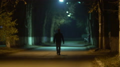 4K. Man walks on the road at night. Shot with Red Cinema Camera Stock Footage