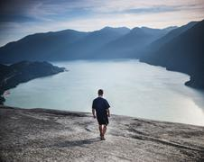 Full length rear view of man walking towards river against Stawamus Chief Stock Photos