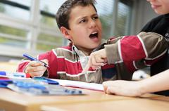 A small boy bothers his friend as he does his school work Stock Photos