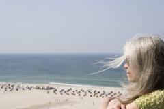A mature adult woman looking out over a beach Stock Photos