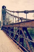 old rusty steel suspension bridge - stock photo