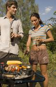 Young couple cooking food on barbeque grill Stock Photos