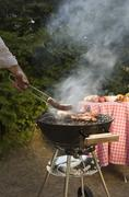 Man cooking meat on a barbeque grill Stock Photos