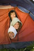 Three friends crowded inside tent Stock Photos
