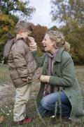 Mother pinching son's nose in park whilst zipper up parka Stock Photos