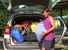 Boy with purple undershirt car baggage charge before departure Stock Photos