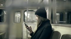 Teen girl rides the subway at night and used smartphone - stock footage