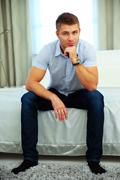 Handsome man in casual cloth sitting on the bed at home Stock Photos