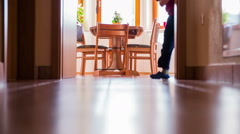 Kid legs behind the wall and running over hallway at home - stock footage
