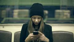 Teen girl rides the subway at night and used smartphone Stock Footage
