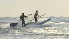 Fishermen trying to shove off paddling against the waves - stock footage