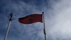 Red Isle of Man flag waving in the wind, manx, blue sky with white clouds Stock Footage