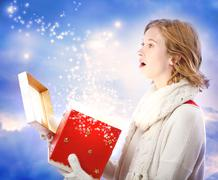 Young woman opening magical christmas gift Stock Photos