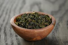 Oolong green tea in olive bowl Stock Photos