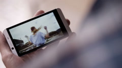 Stock Video Footage of Man Holding Smartphone And Watching Video Of Spinning Girl