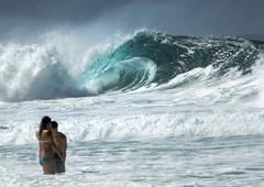 People standing in ocean and huge ocean wave in background Kuvituskuvat
