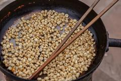 Vietnam, Hanoi, Vietnamese snack food being roasted in iron skillet with - stock photo