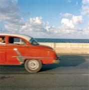 Cuba, Ciudad de La Habana, Havana, Side view of vintage car driving along - stock photo