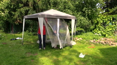 Father and son people attach protective tent bower net in garden - stock footage