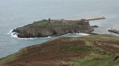 Peel castle from a distance with sea around it, waves splashing against rocks Stock Footage