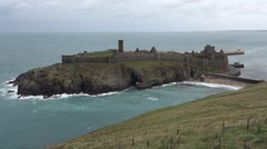 Peel castle with ocean around it, beach visible and many seabirds flying Stock Footage