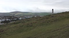 Small village between green hills with tall tower sticking up, Peel,Isle of Man Stock Footage