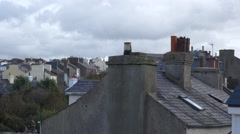 UK Rooftops and chimneys in a British village, cloudy day, smoke comes out Stock Footage