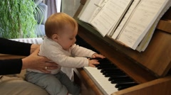 Cute 10-month-old girl trying to play the piano at home - Real Sound Stock Footage