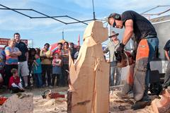 Chainsaw sculptor carves dog out of wood Stock Photos