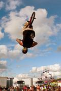 man flips upside down performing bmx stunt at fair - stock photo