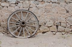 Texas wagon wheel against adobe wall Stock Photos