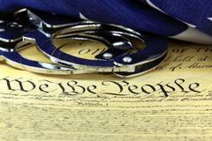 Handcuffs and American flag on US Constitution - Fourth Amendment Stock Photos