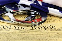 Handcuffs and American flag on US Constitution - Fourth Amendment - stock photo