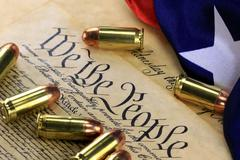 Stock Photo of US Constitution Bill of Rights with 45 caliber bullets and American flag
