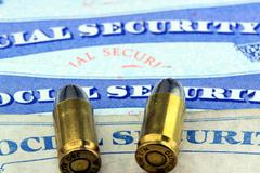 Ammunition bullets laying on social security card - stock photo