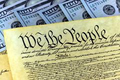 US Constitution with One Hundred Dollar Bills sitting above it - stock photo