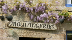 Woman buying bread from a boulangerie - Locronan France Stock Footage