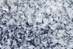 ice crystals of frozen water on a dark surface - stock photo