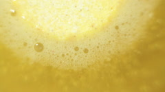 Yellow effervescent tablet bubbling in water Stock Footage