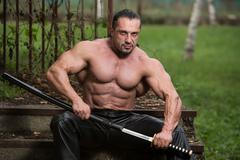 Strong man with samurai sword Stock Photos
