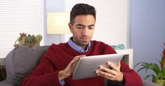 Mexican guy using his tablet on couch Stock Photos
