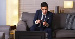 Mexican businessman playing video games at home Kuvituskuvat