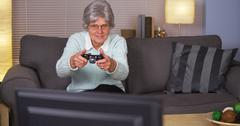 Elderly woman playing videogames Stock Photos