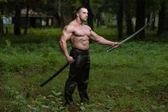 Portrait of a muscular ancient warrior with sword Stock Photos