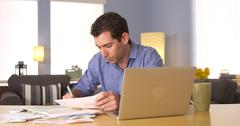 Stock Photo of Man doing his taxes at desk