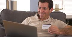 Man typing in credit card information on laptop Stock Photos