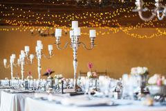 Wedding reception hall with decor including candles, cutlery and crockery Stock Photos