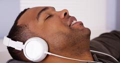 Black man listening to music with headphones - stock photo