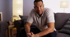 Attractive African bachelor sitting on couch Stock Photos
