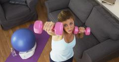 Pretty girl working out in living room - stock photo